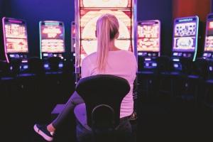Erwachsene Frau vor einem Spielautomaten in einem Casino